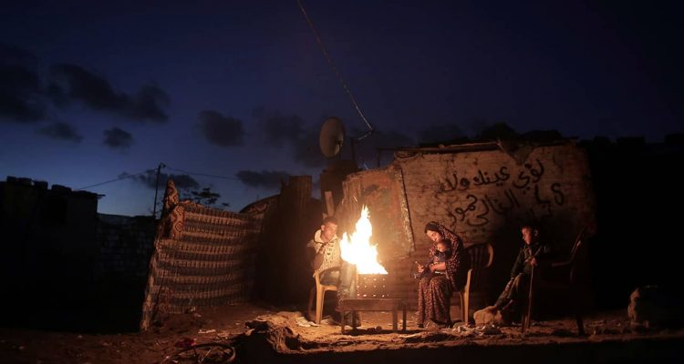 Photo of a Palestinian family outside of their makeshift house