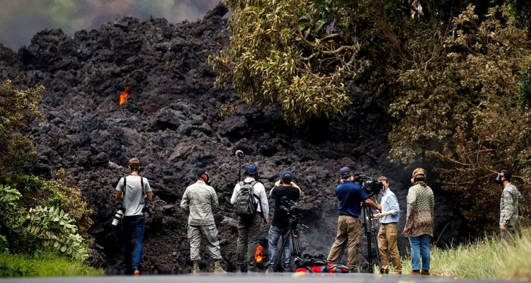Photo of members of the media recording the wall of lava in Pahoa, HI