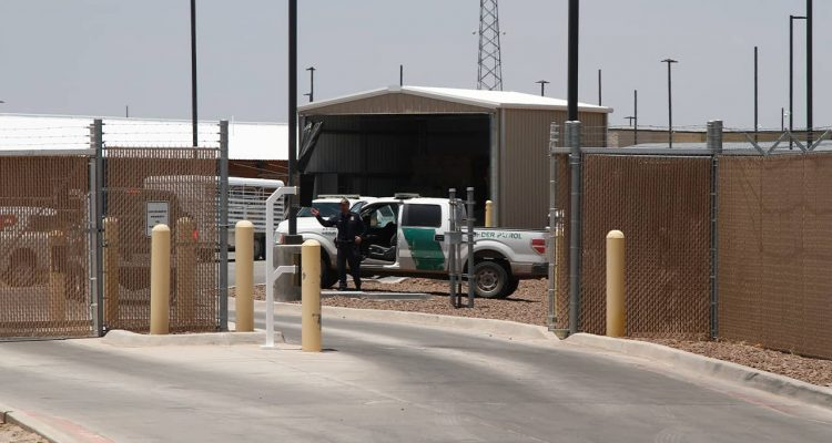 Photo of an officer guarding the entrance to the Border Patrol station in Clint, Tx.