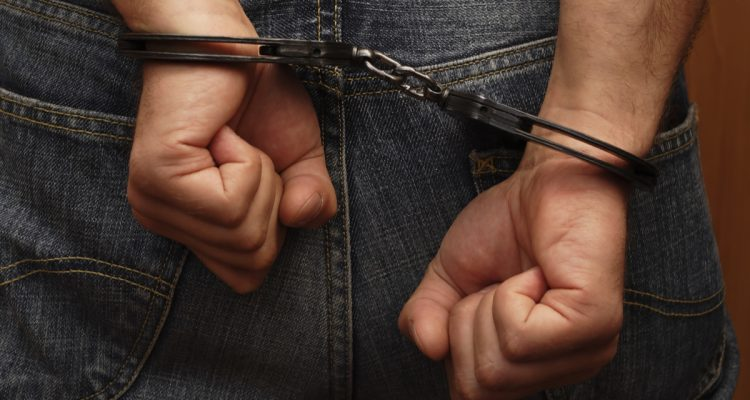 Shutterstock photo of man in handcuffs with back to camera
