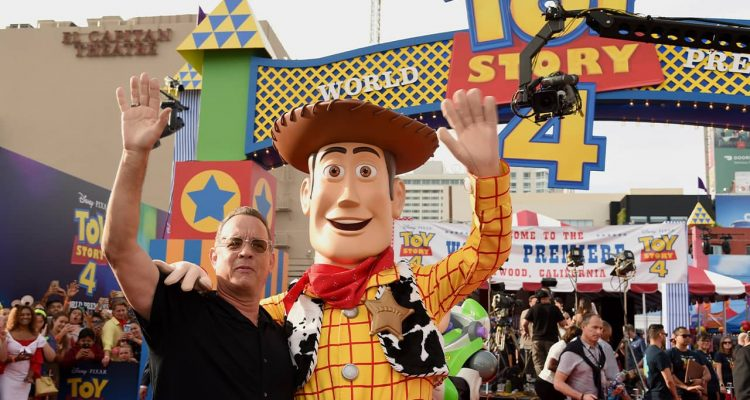 Photo of Tom Hanks posing with his character, Woody