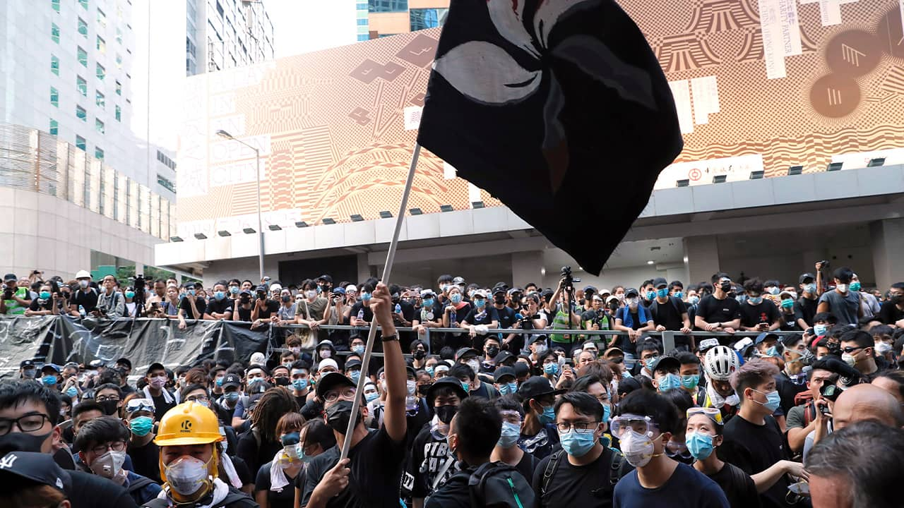 Photo of a protestor waving a black version of the Hong Kong flag