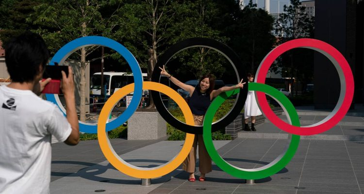 Photo of Tokyo resident taking a picture of his wife with the Olympic rings in Tokyo