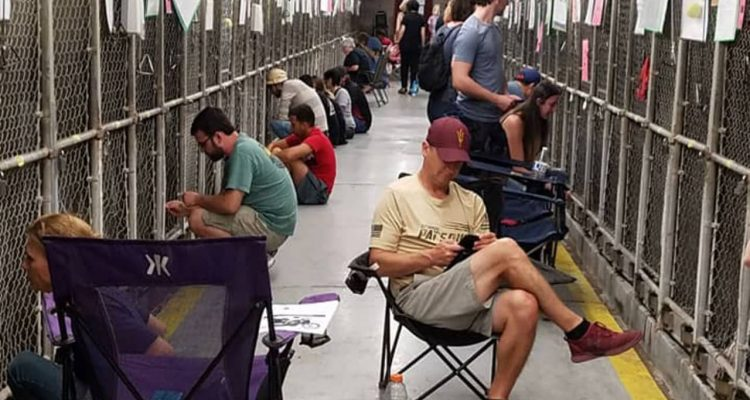 Photo of people sitting in the animal shelter in Phoenix, comforting dogs during 4th of July fireworks