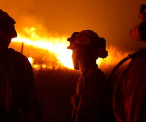 Photo of CDCR inmates standing guard as flames from the Butte fire approach a containment line
