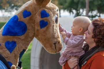 Photo of Valley Children's Hospital mascot George the giraffe and a patient
