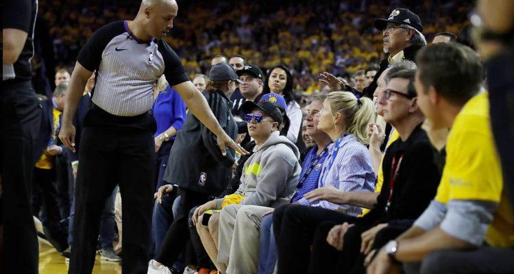 Photo of referee Marc Davis gestures toward Warrior investor Mark Stevens