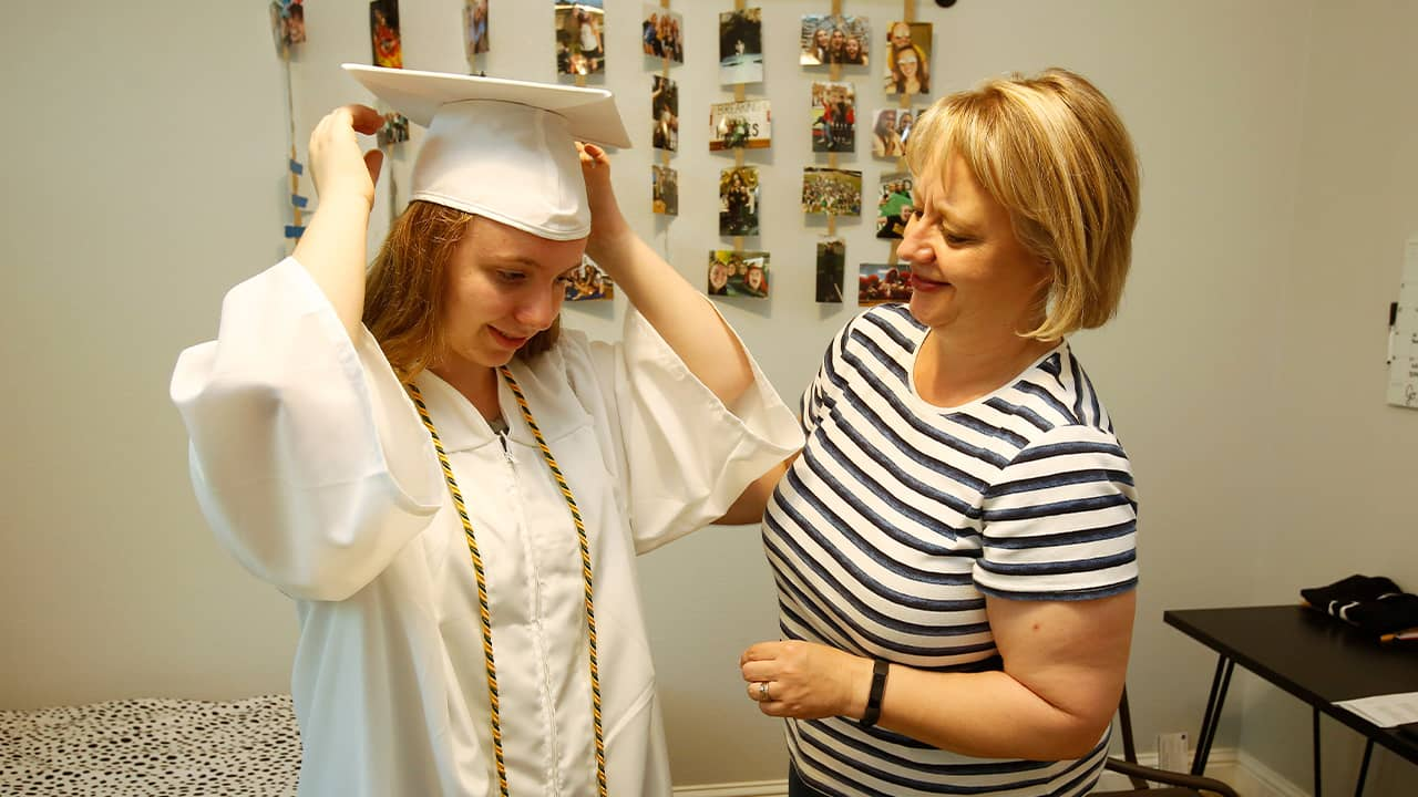 Photo of Emilee Taylor trying on her graduation cap and gown with her mother