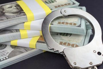 Photo of handcuffs and $100 bills