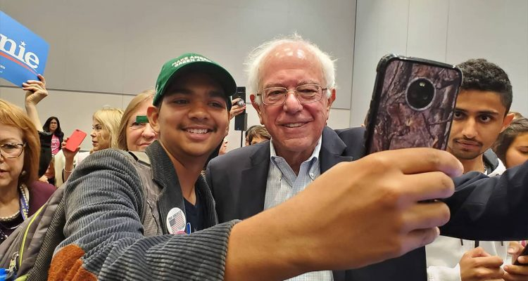 Photo of man snapping a photo with Sen. Bernie Sanders
