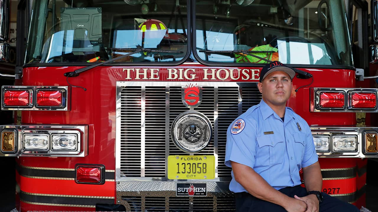 Photo of firefighter Jimmy Reyes next to his firetruck in Orlando, Fla.
