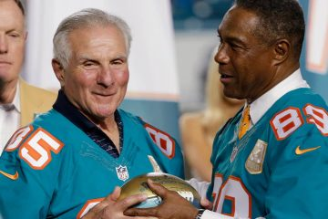 Miami Dolphins player Nick Buoniconti (85) is presented a football by former player and current Dolphins senior vice president of special projects and alumni relations, Nat Moore