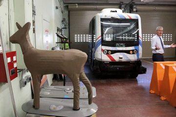 Photo of Randy Iwasaki with an autonomous bus