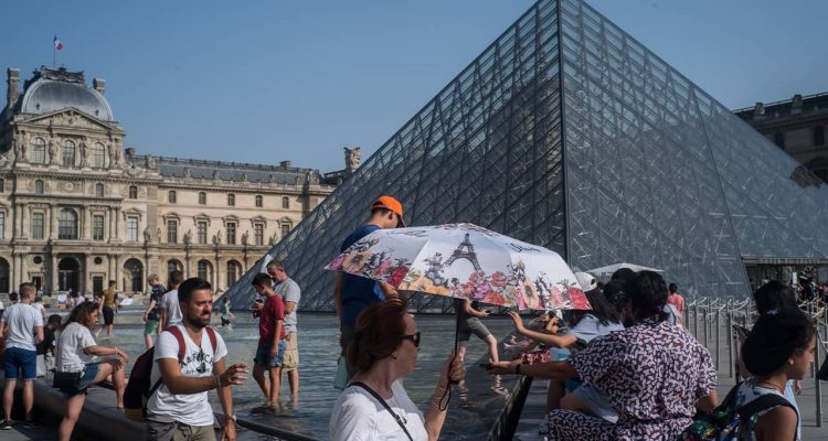 Photo of people cooling next tot he fountain at Louvre Museum in Paris