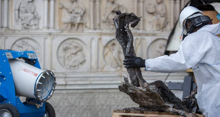Photo of worker cleaning debris at the Notre Dame Cathedral in Paris