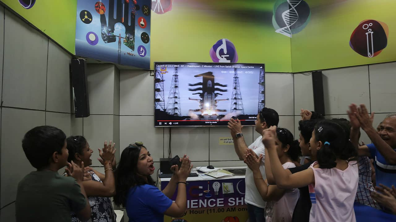 Photo of Indians cheering as they watch the launch on a screen