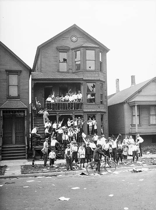Photo of a crowd gathered at a house that has been vandalized and looted during the race riots in Chicago