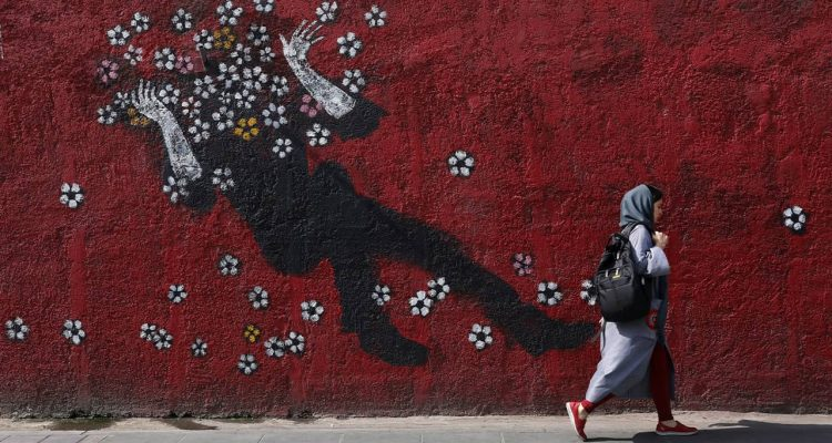 Photo of a woman walking past a mural in downtown Tehran