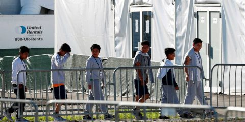 Photo of children lining up to enter a tent at the Homestead Temporary Shelter for Unaccompanied Children in Homestead, Fl.