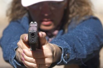 Photo of school secretary aiming a pistol at a shooting range