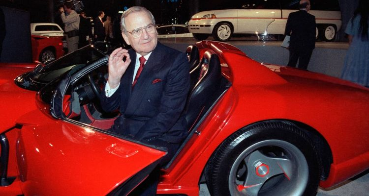 Photo of Lee Iacocca sitting in a 1990 Dodge Viper sports car in 1990