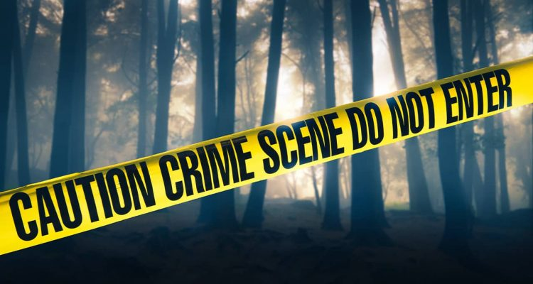 Shutterstock photo of crime scene tape in front of trees in a rural location