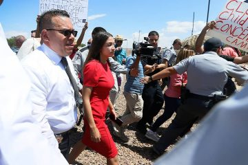 Rep. Alexandria Ocasio-Cortez being escorted after touring the Border Patrol station in Clint, Tx.