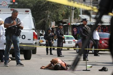 Photo of a bloodied man laying in the street in Mexico