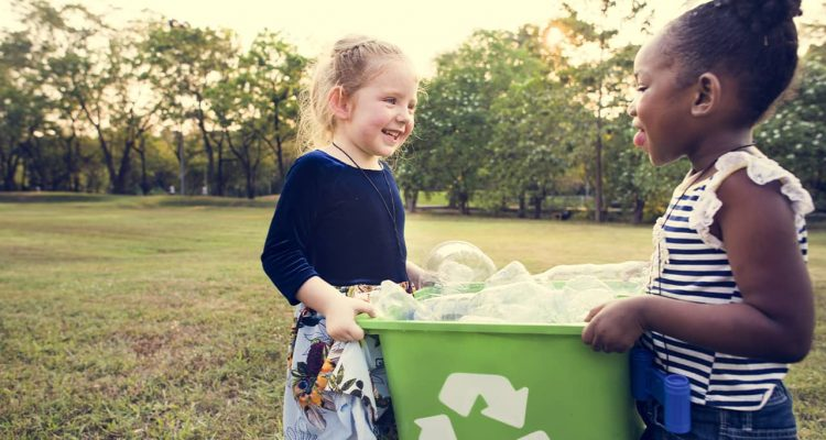 Photo of two young girls holding a recycling bin