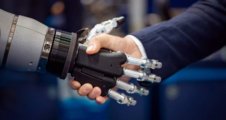 Photo of a robot shaking hands with a businessman