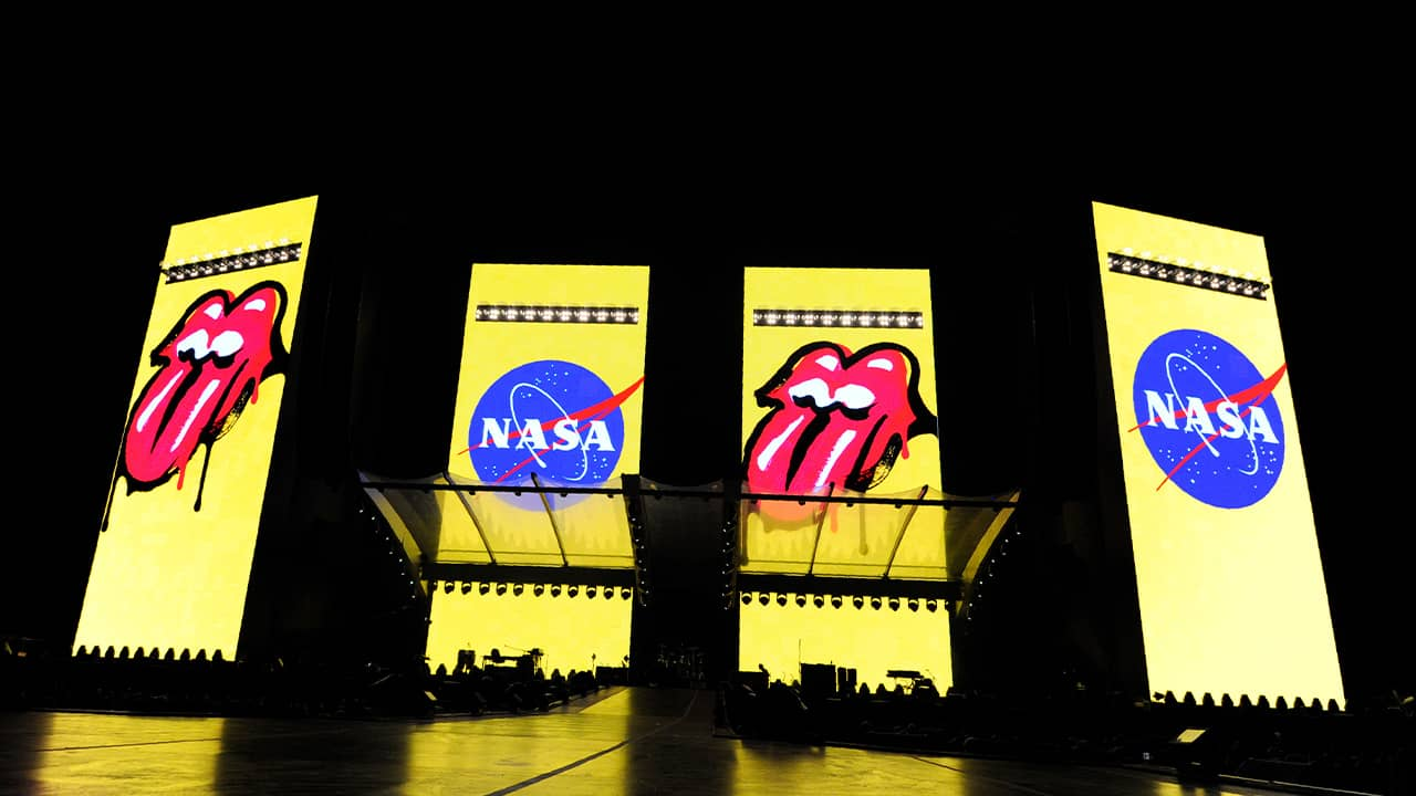 Photo of logos for The Rolling Stones and NASA displayed onstage before their concert at the Rose Bowl