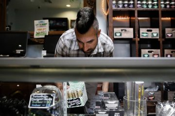 Photo of Jerred Kiloh stocking shelves with cannabis products