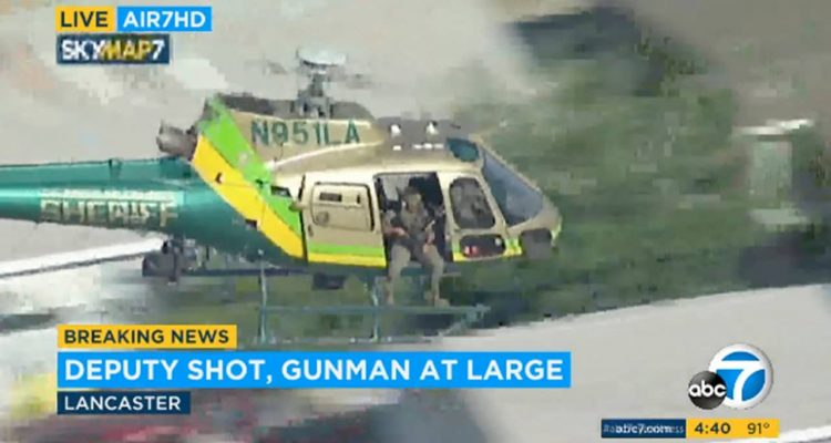 Photo of a sheriff's department helicopter with a sniper in an open door searching for a gunman at large