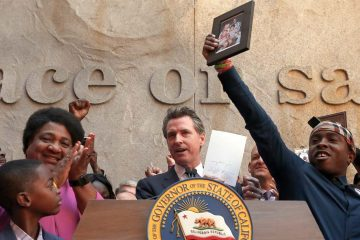 Photo of Gov. Gavin Newsom surrounded by Assemblywoman Shirley Weber and members of the Clark family after the signing of AB 392 lFam