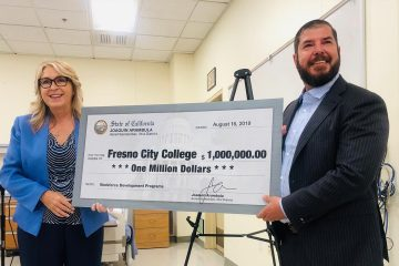 Photo of Carole Goldsmith and Assemblyman Joaquin Arambula holding a check