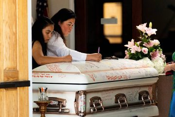 Photo of mourners writing on Keyla Salazar's casket during her funeral