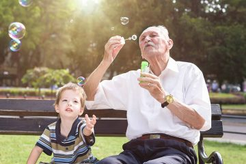 Photo of child with older man blowing bubbles in a park