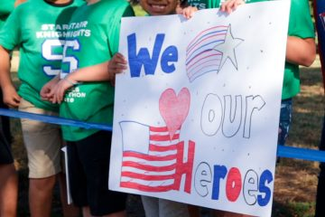 Photo of students holding a homemade sign saluting their heroes