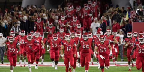 Photo of Fresno State football players running onto the field at Bulldog Stadium