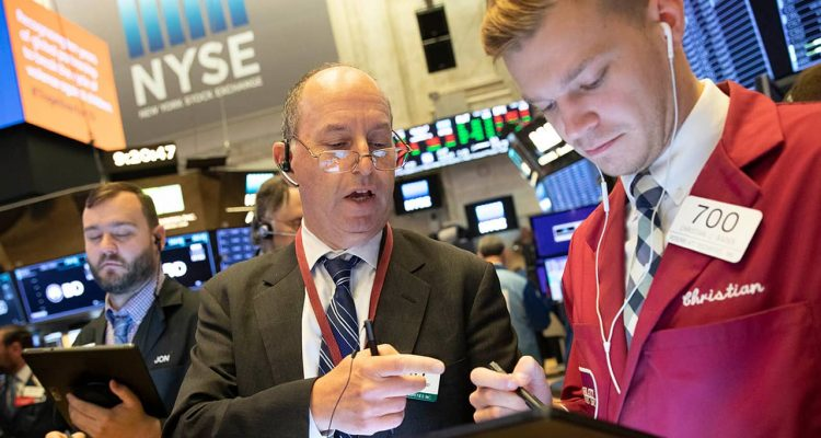 Photo of Gordon Charlop, center, and Christian Bader working at the New York Stock Exchange
