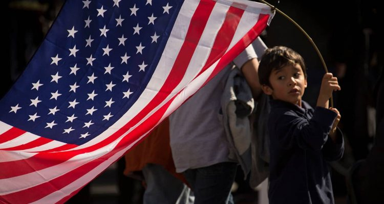 Photo of a young boy holding an American flag