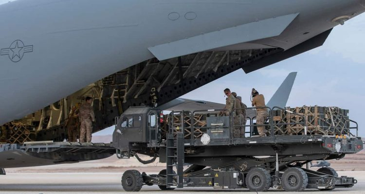 Photo of U.S. service members loading military equipment