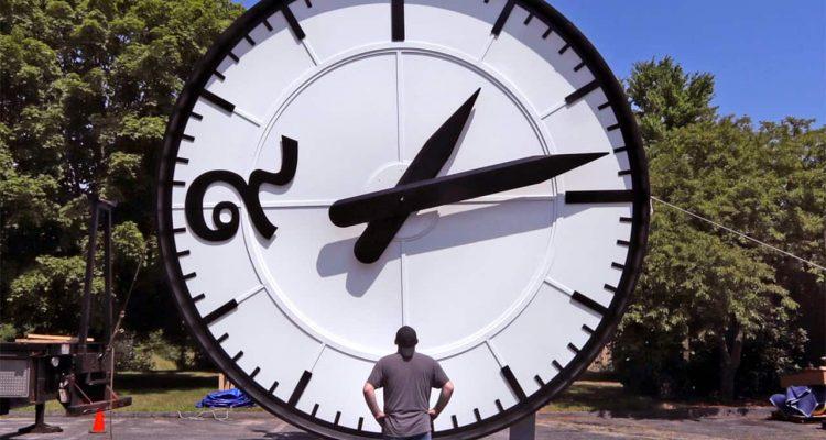 Photo of a man looking up at a big clock