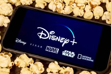 Photo of an iPhone with Disney Plus on the screen surrounded by popcorn