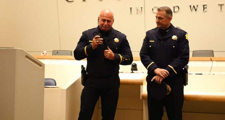 Photo of Jerry Dyer signing off as Fresno Police Chief. He is accompanied by new police chief Andy Hall