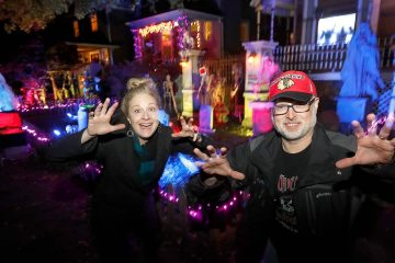 Photo of Beth LeFauve and Nelson Gonzalez posing in front of their decorated homes
