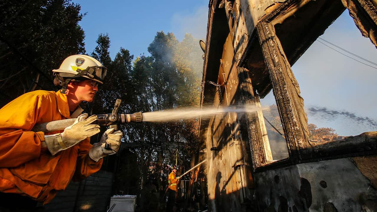 Photo of a firefighter spraying a hose