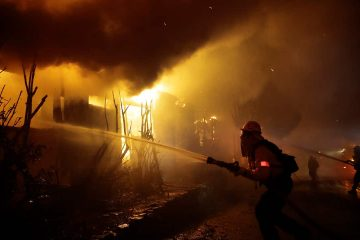 Photo of firefighters trying to hose down flames as homes burn