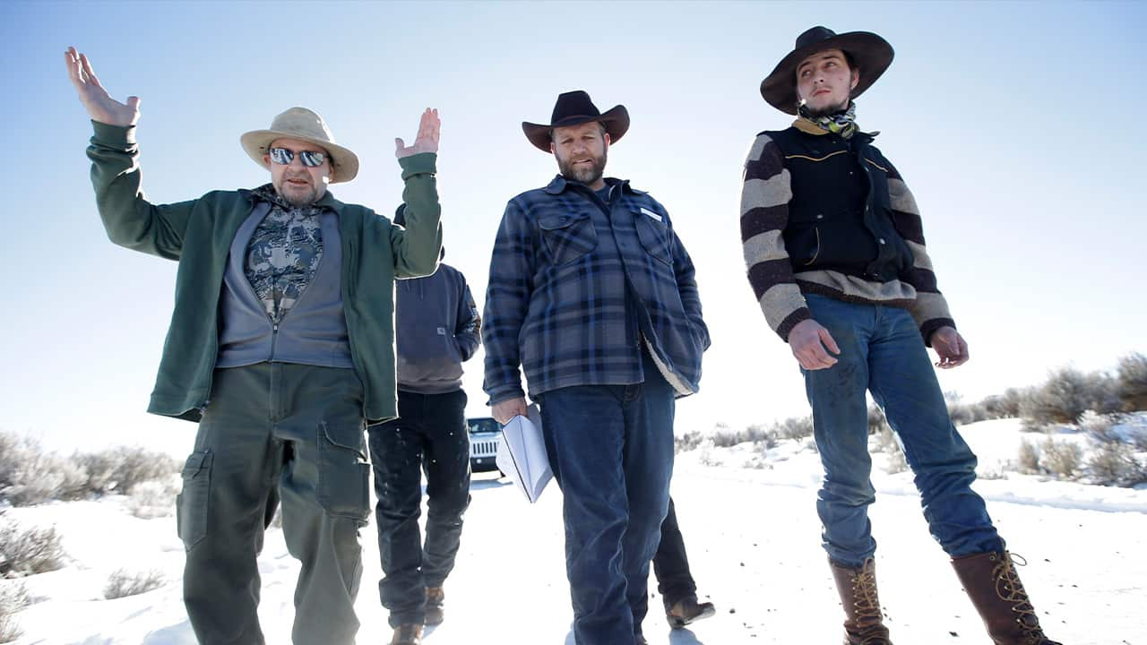 Photo of Burns resident Steve Atkins, left, talking with Ammon Bundy, center, one of the sons of Nevada rancher Cliven Bundy