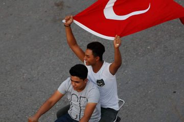 Photo of to men on a motorcycle holding the Turkish flag in the air